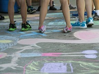 Group of children standing on Road chalk drawings